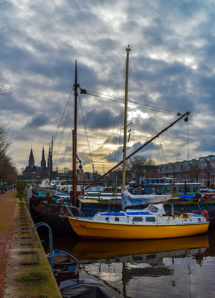A yellow sailboat anchored at Westerdok in Amsterdam makes a nice subject featuring the Posthoornkerk the background.