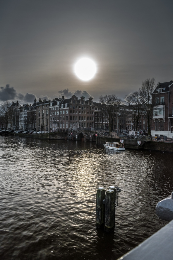 The sun was hiding behind a thin layer of clouds and created this dramatic light reflection on the Amstel canal.
